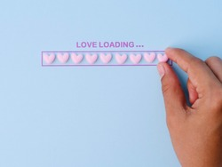 Valentines Day. Love Loading Valentine's hearts with hand putting pink hearts in progress bar on pink background. Happy Valentine's Day Concept.