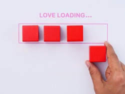 Valentines Day. Love Loading with hand putting wood cube in progress bar on white background. Happy Valentine's Day Concept.