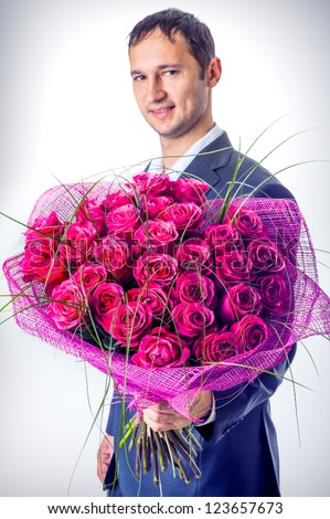 Valentines day. Man holding big bouquet of flowers. Proposal scene