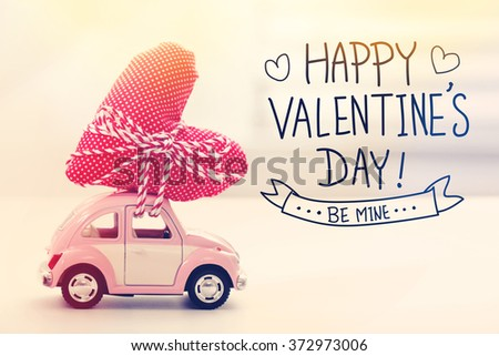 Valentines Day message with miniature pink car carrying a heart cushion
