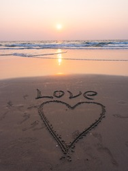 Valentines day on the beach. Gift, celebration, romantic. A heart is drawn on the seashore. The inscription on the beach sand: Love. 14 of February. Sunset on tropical background, seacoast, waves.