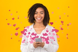 Valentines Day. Portrait of black woman sending and receiving love sms on mobile phone with pink hearts flying up