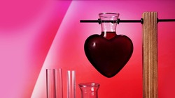 Valentines day potion. Love potion in the shape of a heart on a pink background. Chemical flasks.