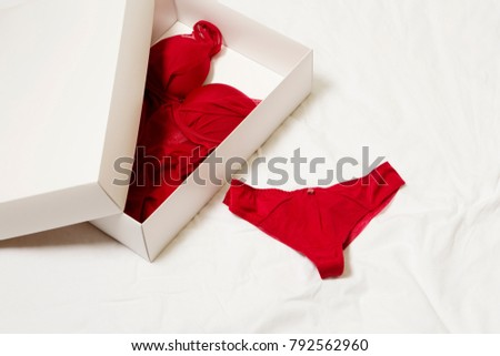 Valentines day present. Red sexy lingerie. Gift box lying on the bed.