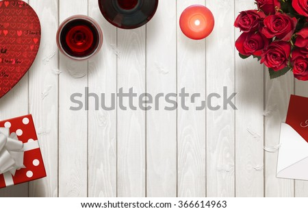 Photo of Valentines day romantic background with gifts, glasses of wine, candle, roses, envelope on wooden table.