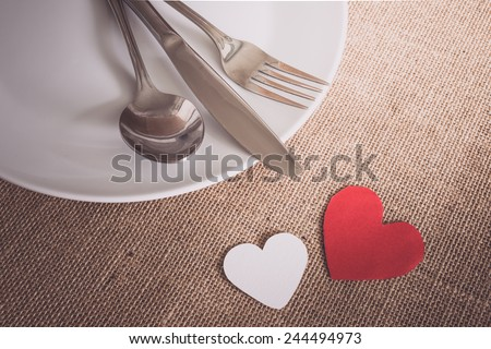 Valentines day set with silverware , white dish, hearts on sackcloth textures