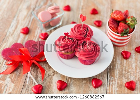 valentines day, sweets and romantic concept - close up of frosted cupcakes, red heart shaped chocolate candies, lollipops and strawberries #1260862567