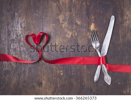 Valentines day table setting with plate, knife, fork, red ribbon and hearts/ Holidays background/ Valentines day background #366265373