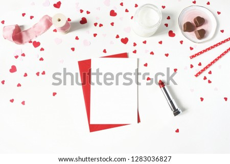 Valentines day, wedding still life scene. Candle, paper confetti, chocolate hearts, lipstick and blank greeting card mockup on white table background. Love concept. Flat lay, top view.  #1283036827