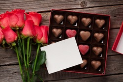 Valentines day with red roses and chocolate box on wooden table. Top view with space for your text