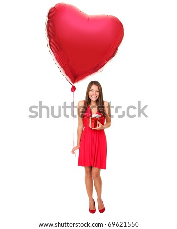 Valentines day woman holding gift and red heart balloon. Cute beautiful young woman smiling in red dress. Asian / Caucasian female model isolated on white background in full length.