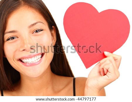 Valentines Day. Woman holding Valentines Day heart sign with copy space. Beautiful mixed race chinese / caucasian model isolated on white background.