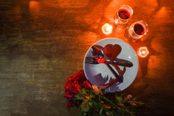 Valentines dinner romantic love concept / Romantic table setting decorated with fork spoon on plate and couple champagne glass wine roses with candlelight on table dinner night light top view