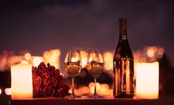 Valentines dinner romantic love concept / Romantic table setting decorated with wine glass roses with candlelight on wooden table and city night light view.
