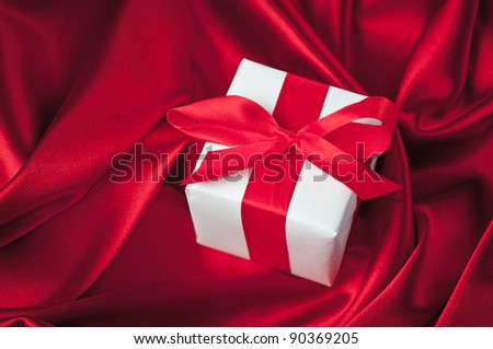 Valentines gift boxes tied with a red satin ribbon bow on red satin background