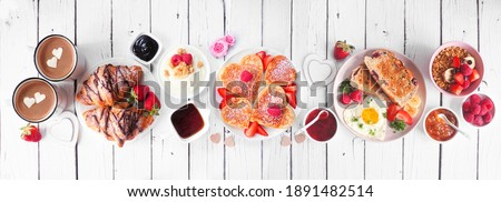 Valentines or Mothers Day breakfast table scene. Above view on a white wood banner background. Heart shaped pancakes, eggs and a variety of love themed food.