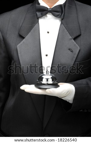 Valet or butler holding service bell in gloved hand in front of body, torso only