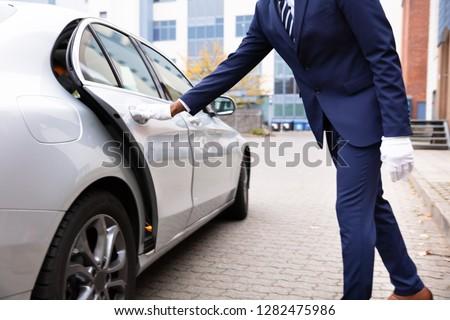 Valet's Hand Opening Grey Car Door On Street Stock photo ©
