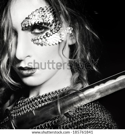 Stock Photo Valkyrie. Closeup portrait of attractive woman with sword blade