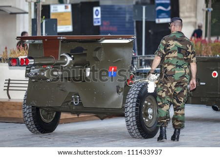 VALLETTA, MALTA - AUG 25 - A soldier inspects and cleans the gun carriage to be used for the state funeral of former Prime Minister Dom Mintoff in Malta on 25 August 2012