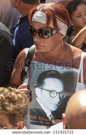 VALLETTA, MALTA - AUG 25 - A woman holds a picture of a young Dom Mintoff close to her heart during the state funeral of the former Prime Minister of Malta in Valletta on 25 August 2012