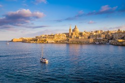 Valletta, Malta - Sail boat at the walls of Valletta with St.Paul's Cathedral and beautiful blue sky