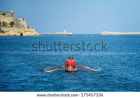 VALLETTA, MALTA - SEPTEMBER 8: traditional boats regatta in Valletta in Mediterranean sea with New Harbour Bridge and blue sky background on Sep 8, 2013. Popular regatta in Malta. Traditional sport