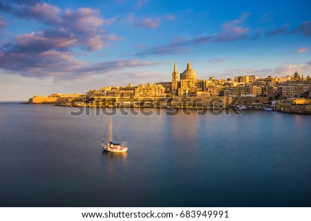 Stock Photo Valletta, Malta - St.Paul's Cathedral in golden hour at Malta's capital city Valletta with sailboat and beautiful colorful sky and clouds
