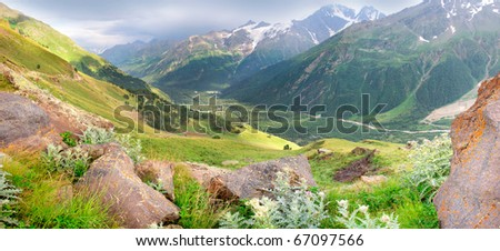 Valley amongst mountains with wood and green meadow. Panorama