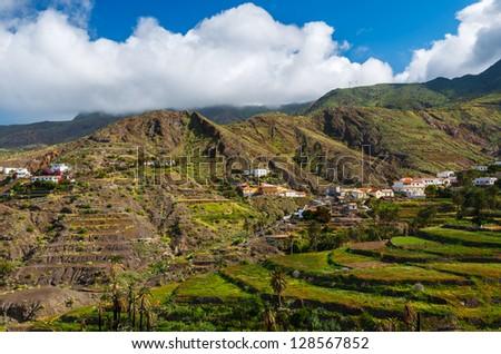 Valley mountains palm trees white clouds blue sky, near Alojera village, La Gomera, Canary Islands