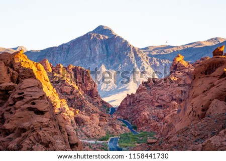 Valley of Fire highway passing through glowing orange mountains during sunset #1158441730