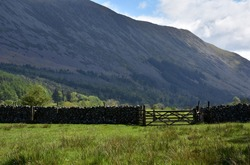 Valley with a rustic stonewall and gate at the base of a fell.