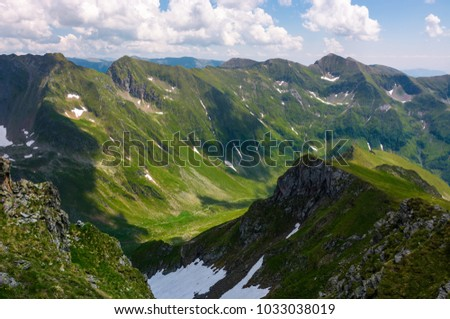 valley with snow in summer mountains. gorgeous mountainous landscape of Carpathians. rocky cliffs and grassy hillsides under a cloudy sky. Fagaras ridge of Southern Carpathian mountains, Romania #1033038019