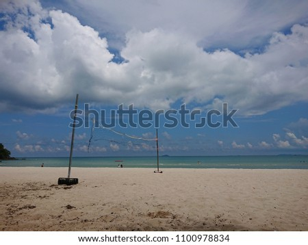 Valleyball nets on beach with cloudy sky.