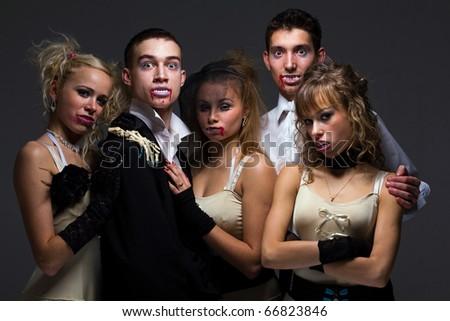 Vampire family posing on a gray background