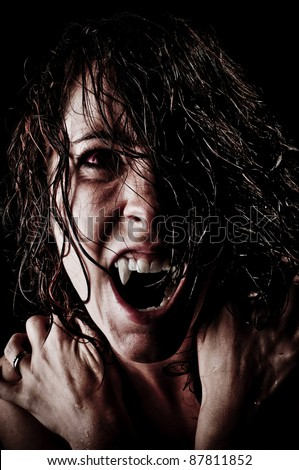 Vampire with long wet hair, fangs and red eyes ready to feed in the night - stock photo