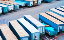 Van containers and Cargo Shipping in shipyard in Mediterranean Sea at port at Cagliari, Sardinia island, Italy summer. Truck trailer. Wagons of vans. Mixed media.