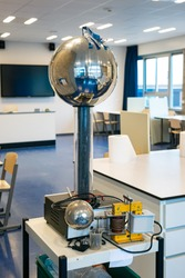 Van de Graaff generator:  an electrostatic generator which produces very high voltage direct current (DC) electricity at low current levels. Used as demonstration in physics class.