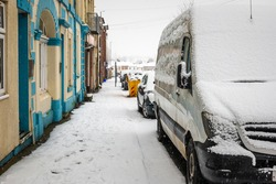 Van parked on british street under winter snow fall in england uk