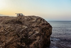 Van with opened boot parked on a cliff on sunset near the ocean. Portugal, Europe