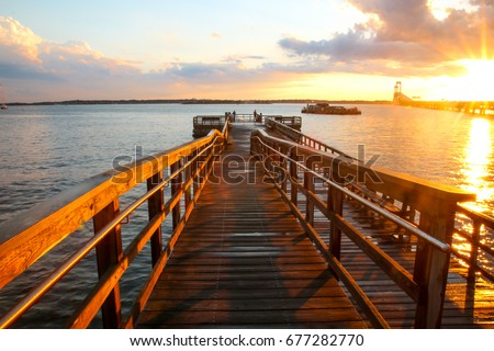 Van Zant Pier after a rainstorm in Newport, Rhode Island. The wooden platform is wet from the rain, during the sunset. In the background is the Newport Bridge and storm clouds. Popular with fishermen #677282770