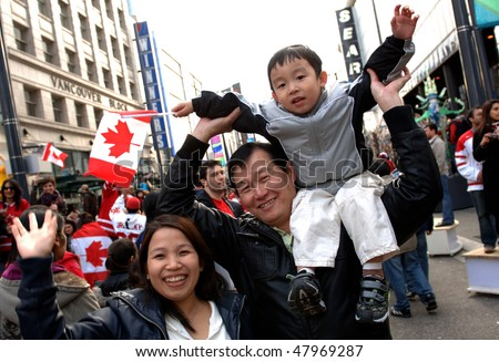 VANCOUVER, BC, CANADA - FEBRUARY 28: Canadian family enjoys festive atmosphere in Vancouver during 2010 Winter Games, February 28, 2010 in Vancouver, BC, Canada