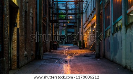Vancouver, British Columbia - Canada. Empty back alley on one of the streets of Vancouver, British Columbia. Canada. Chilly night just after a rain. Dangerous place to hang around.