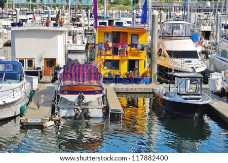 VANCOUVER, CA - JULY 08: Beautiful Painted Houseboats in Vancouver Marina on July 8, 2008 in Vancouver, Canada. Famous houseboats at the Coal Harbour Marina full of yachts of the rich and famous