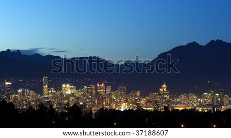 Vancouver Canada at night set in between the trees and the North Shore mountains.