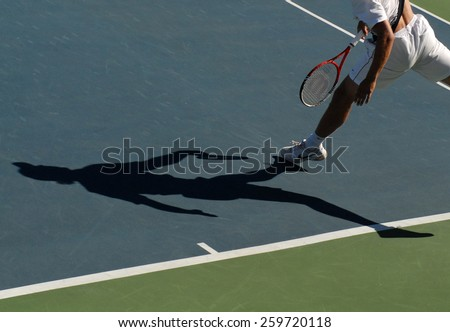 VANCOUVER, CANADA - AUGUST 7, 2014: An athlete casts a shadow during tennis match in Stanley Park in Vancouver, Canada, on August 7, 2014.