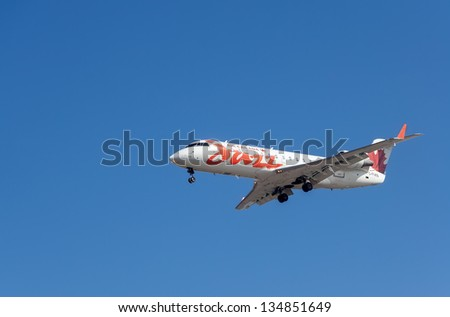 VANCOUVER, CANADA - MARCH 28: Air Canada Jazz plane on final approach to Vancouver International Airport on March 28, 2013. It is the only airline serving Canada 10 provinces and 2 territories. - stock photo