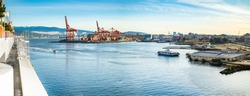 Vancouver Harbour panorama early mornings, on a sunny day. Waterfront city skyline with industry. A seabus ferry is leaving the waterfront station. Industrial cranes with cargo containers and tanker.