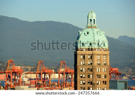 Vancouver Historic Beaux-Arts style Sun Tower and North Vancouver city skyline across Vancouver Harbour, Vancouver, British Columbia, Canada.