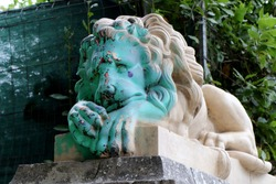 Vandalized statue of a sad lion. Sad green colored face with spray paint